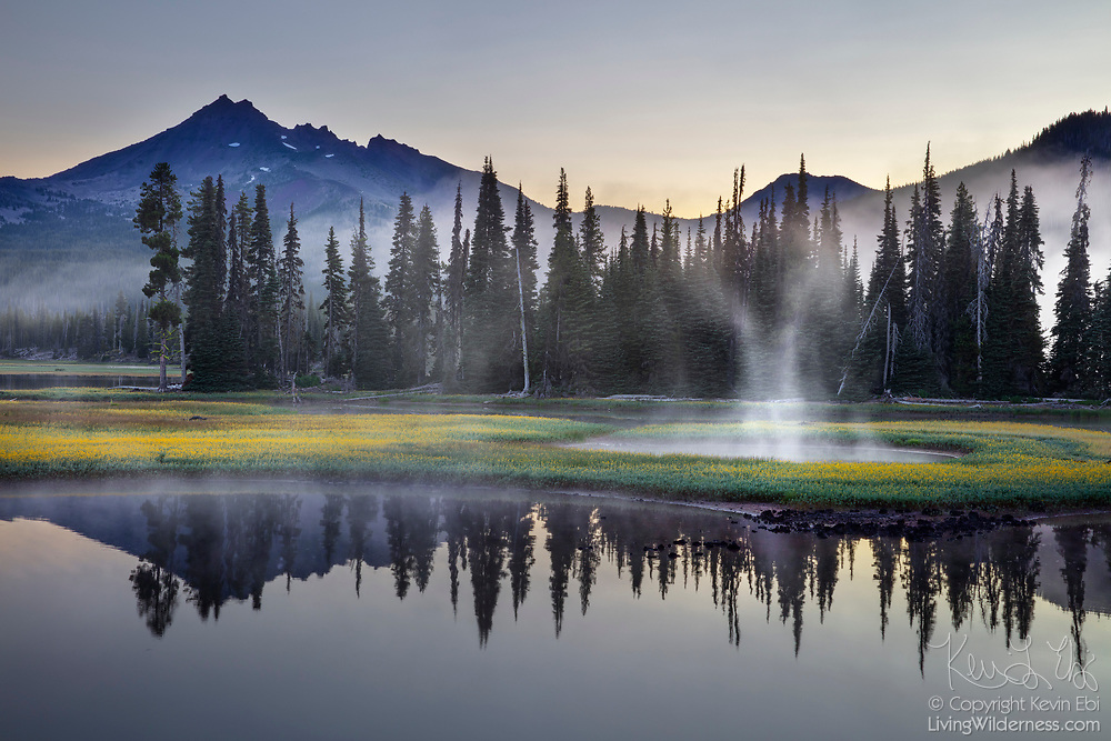 Steam fog seems to erupt from a small pool on an island within Sparks Lake in the Deschutes National Forest near Bend, Oregon. The island is covered with yellow spear-leaf arnica (Arnica longifolia) flowers in mid-summer. Broken Top Mountain rises in the back left of the image. Broken Top, which stands 9,177 feet (2,797 meters) tall, is a stratovolcano that last erupted about 100,000 years ago and has since been eroded by glaciers.