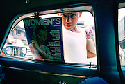 Boy sells magazines at car windows in Manila, Philippines