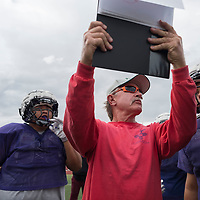 Patriots assistant head coach Gary Schuster holds up the next play for the first team offense. The purpose of this is to see how well they understand the plays and individual assignments before their team takes on the Aztec Tigers at home on Friday at Miyamura High School in Gallup, NM.