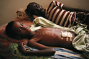 """Wounded boy with his father at the """"Villa Hospital"""", a private home turned into a hospital in the north sector (Ali Mahdi controlled sector) of Mogadishu, the war-torn capital of Somalia where 30,000 died between November 1991 and March 1992."""