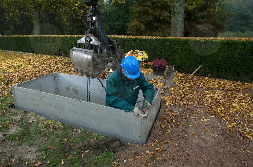 Nederland Hoogvliet 29 oktober 2007 .Grafdelvers maken een nieuw graf op begraafplaats.  De bak waar de lift voor de kist in komt wordt geplaatst .Foto David Rozing/ Hollandse Hoogte