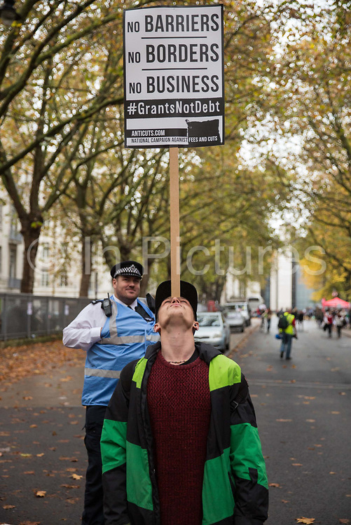 A police liaison officer watches a student balancing a placard on his forehead before the National Demonstration for a Free Education on 4th November 2015 in London, United Kingdom. The demonstration was organised by the National Campaign Against Fees and Cuts NCAFC in protest against tuition fees and the Government's plans to axe maintenance grants from 2016.