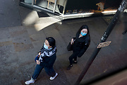 Two young women from London's Chinese community in Chinatown walk along Shaftesbury Avenue in London's West End wearing surgical face masks during the worldwide Coronavirus pandemic, on 12th March 2020, in London, England.