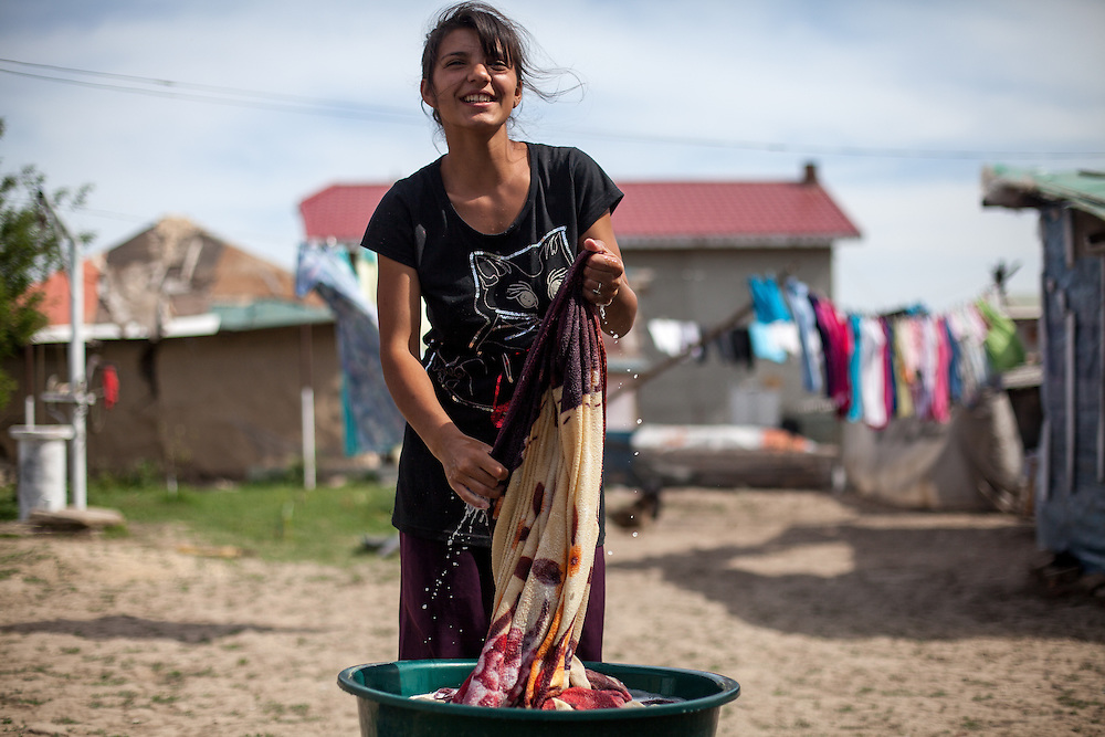 """A young woman washes laundry in the open air in Frumuşani. Drop out rates from education for young Roma students are still high. """"Better access to schools and improving educational outcomes are key,"""" explains Costel Bercus, of the Roma Education Fund."""