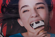 A detail of an advert - a picture of a girl enjoying an ice cream cone with chocolate chips seemingly the shape of bad teeth, on 12th July 2016, at Estoril, near Lisbon, Portugal. Estoril is a town and a former civil parish in the municipality of Cascais, Portugal, on the Portuguese Riviera.