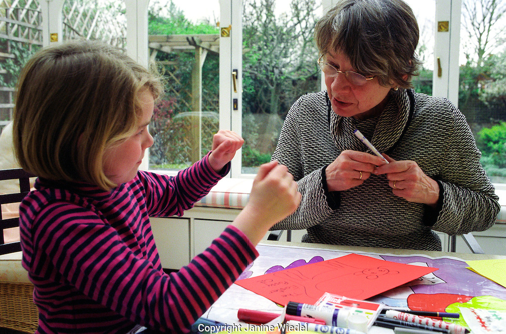 grandmother drawing with grand daughter at home.