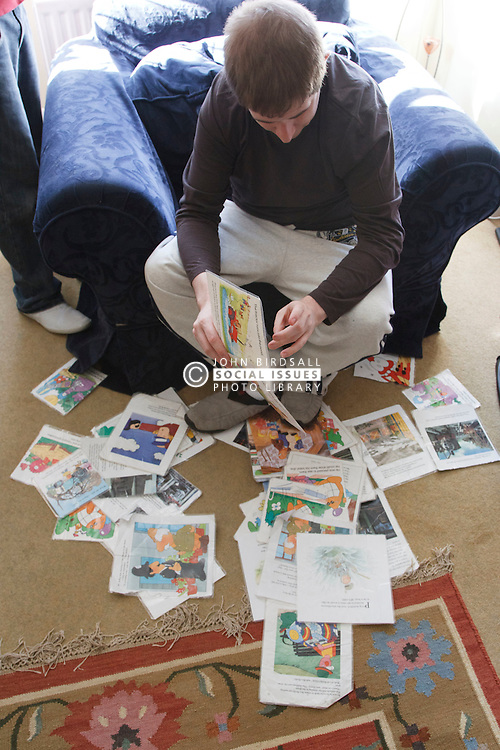 Young man with autism with collection of pages from children's books. Cleared for Mental Health issues.