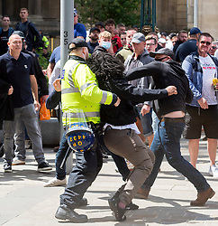 © Licensed to London News Pictures; 13/06/2020; Bristol, UK. A black man appears to get punched and injured at an 'All Lives Matter' protest rally at the Cenotaph war memorial  in Bristol city centre. The injured man is then led away by police. The event comes nearly a week after the Black Lives Matter march when the statue of Bristol slave trader and philanthropist Edward Colston was pulled down from a plinth nearby and thrown into Bristol harbour. Despite the restrictions due to the Covid-19 coronavirus pandemic, Black Lives Matter protests have occurred across the world in memory of George Floyd, a black man who was killed on May 25, 2020 in Minneapolis in the US by a white police officer kneeling on his neck for nearly 9 minutes. Photo credit: Simon Chapman/LNP.