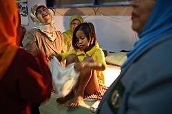 A young girl puts her panties back on after being circumcised in Bandung, Indonesia on April 23, 2006. The families of 248 girls were given money to have their children circumcised in a mass circumcision celebration timed to honour the Prophet Mohammed's birthday. While religion was the main reason for circumcisions, it is believed by some locals that a girl who is not circumcised would have unclean genitals after she urinates which could lead to cervical cancer. It is also believed if one prays with unclean genitals their prayer won't be heard. The practitioners used scissors to cut the hood and tip of the clitoris. The World Health Organization has deemed the ritual unnecessary and condemns such practices.