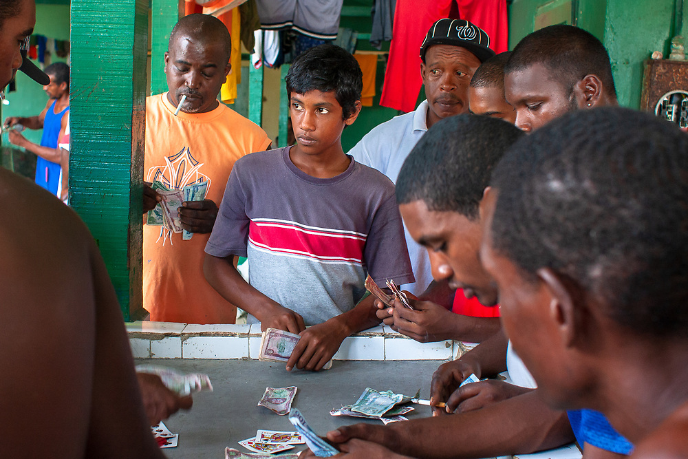Maracas Bay, Trinidad   2009<br /> After preparing and selling the day's catch, fishermen gamble at wapee, based on the English card game all fours.