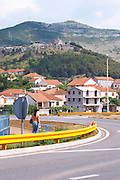 Street scene in Trebinje, a main road and a woman walking, the monastery Gracanica on the historic hill known as Crkvina in the background. Trebinje. Republika Srpska. Bosnia Herzegovina, Europe.