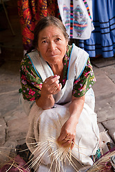 North America, Mexico, Oaxaca Province, Oaxaca, woman weaving straw baskets in market