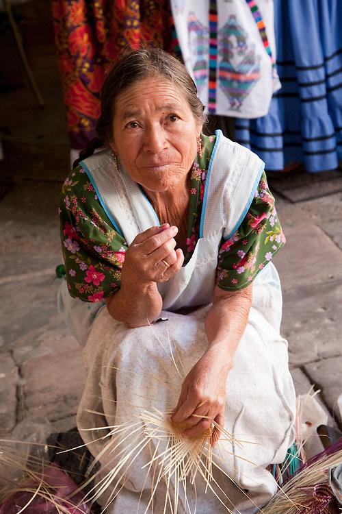 North America, Mexico, Oaxaca Province, Oaxaca, woman weaving straw baskets in market