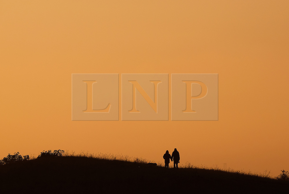 © Licensed to London News Pictures.02/11/15<br /> Redcar, UK. <br /> <br /> A couple walk their dog through Coatham Marshes as the sun sets in Redcar this evening.<br /> <br /> Photo credit : Ian Forsyth/LNP