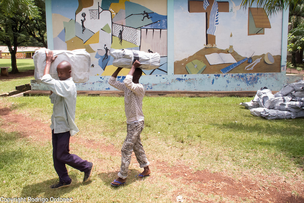 Temporary workers hired by Save the Children walk past a school's wall painting as they unload a truck with relief items in Man, western Côte d'Ivoire. <br /> Save the Children chartered a cargo plane carrying urgently needed items, including plastic sheeting, mosquito nets, buckets and water purification tablets. The children's charity will be handing out these basic supplies to 5,000 families displaced by conflict in western Côte d'Ivoire to help prevent the spread of diseases.