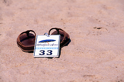 A tag for an umbrella lays on a pair of sandals, Friday, Aug. 16, 2019 at Henlopen Acres Beach Club in Rehoboth Beach, Del. (Photo by D. Ross Cameron)
