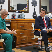 Florida Governor Ron DeSantis talks with Dr. Raul Pino, Director of Florida Department of Health in Orange County, on how to safely reopen Florida salons with small business owners during a roundtable at OhSoooJazzy Hair Salon in Orlando, Florida on Saturday, May 2, 2020. (Alex Menendez via AP)