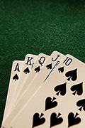 A royal flush poker hand in spades sitting on a green felt table