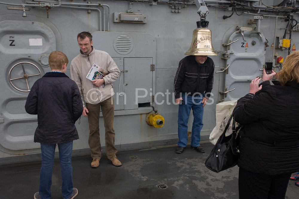 Visitors admire the ship's bell while touring the top deck on-board the Royal Navy's aircraft carrier HMS Illustrious during a public open-day in Greenwich. Illustrious docked on the river Thames, allowing the tax-paying public to tour its decks before its forthcoming decommisioning. Navy personnel helped with the PR event over the May weekend, historically the home of Britain's naval fleet.