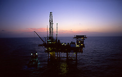 Stock photo of an offshore jack-up drilling rig at sunset in gulf of mexico.