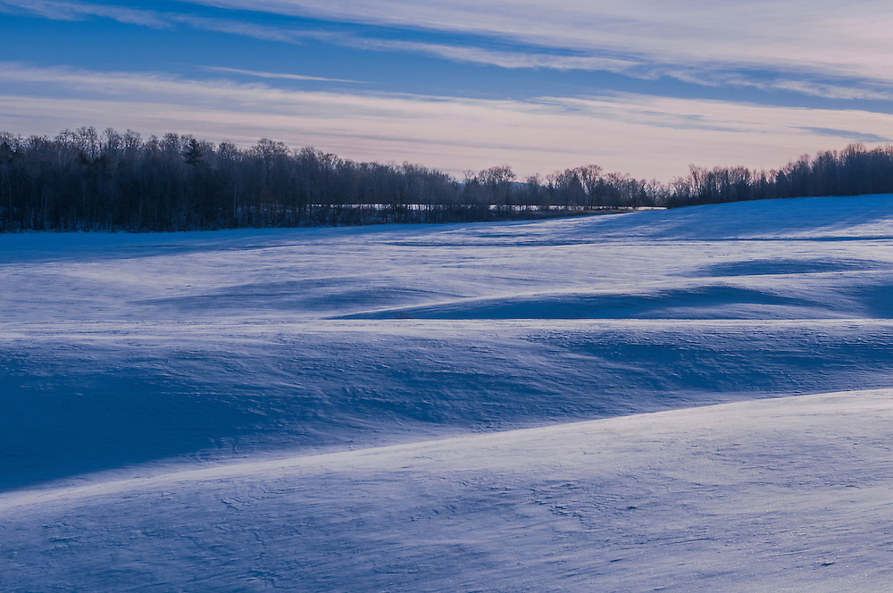 Snow covered landscape of undulating hillocks and dips of winter field, view to treeline, Fairfield, VT