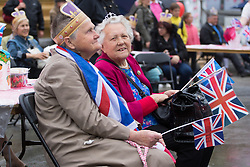 Trafalgar Square, London, June 12th 2016. Rain greets Londoners and visitors to the capital's Trafalgar Square as the Mayor hosts a Patron's Lunch in celebration of The Queen's 90th birthday. PICTURED: Two pensioners enjoy the entertainment on stage.