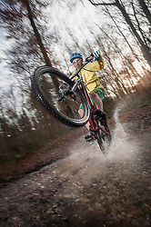Mountain Biker rides on the rear wheel through a stream in the forest, Bavaria, Germany
