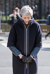 © Licensed to London News Pictures. 22/03/2018. London, UK. British Prime Minister THERESA AMY bows her head after placing a floral tribute at Parliament Square, outside the Houses of Parliament in Westminster, London on the one year anniversary of the Westminster Bridge Terror attack in which lone terrorist killed 5 people and injured several more, in an attack using a car and a knife. The attacker, 52-year-old Briton Khalid Masood, managed to gain entry to the grounds of the Houses of Parliament and killed police officer Keith Palmer. Photo credit: Ben Cawthra/LNP
