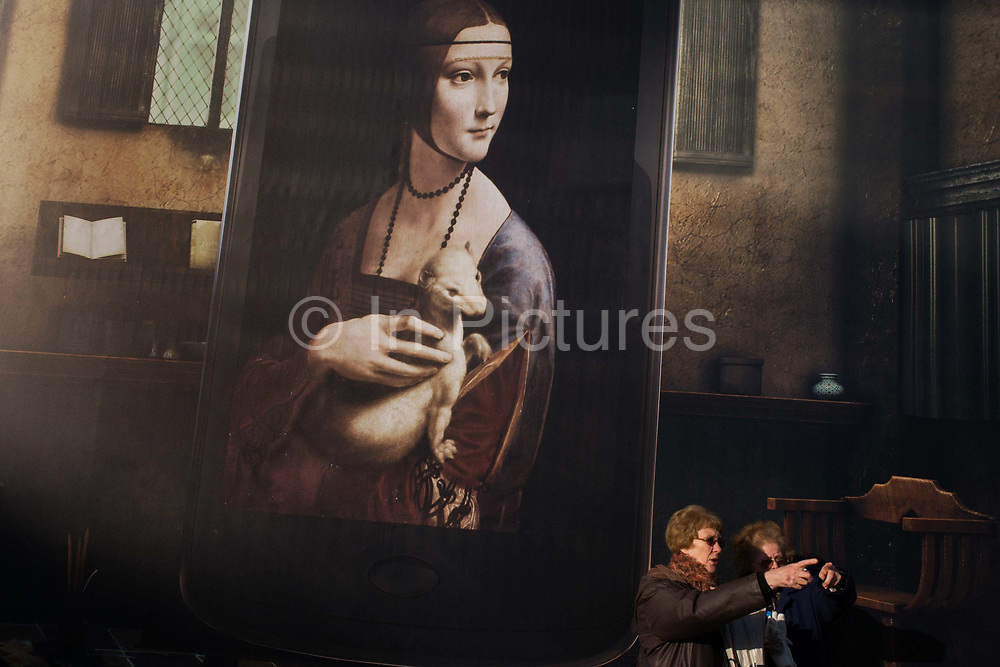 Billboard advertising Leonardo da Vinci's Portrait of Cecilia Gallerani (Lady with an Ermine) above London tourists at National Gallery. The da Vinci portrait is identified as 16 year-old Cecilia Gallerani, probably painted at a time when she was the mistress of Lodovico Sforza, Duke of Milan, and Leonardo was in the service of the Duke. The giant mural is in Trafalgar Square to publicise the very popular 'Leonardo da Vinci: Painter at the Court of Milan' exhibition of 2011-12.
