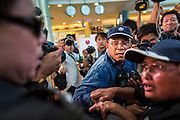 """01 JUNE 2014 - BANGKOK, THAILAND:  A Thai man who protested against the military coup is chased by police in Terminal 21 shopping mall in Bangkok. The Thai army seized power in a coup that unseated a democratically elected government on May 22. Since then there have been sporadic protests against the coup. The protests Sunday were the largest in several days and seemed to be spontaneous """"flash mobs"""" that appeared at shopping centers in Bangkok and then broke up when soldiers arrived. Protest against the coup is illegal and the junta has threatened to arrest anyone who protests the coup. There was a massive security operation in Bangkok Sunday that shut down several shopping areas to prevent the protests but protestors went to malls that had no military presence.   PHOTO BY JACK KURTZ"""