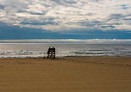 Lifeguards at the lifeguard station on an empty beach with the ocean churning after a summer squall