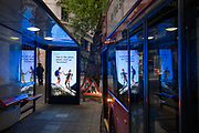 As a London bus pauses in Aldwych bus stop, a digital ad promoting Austrian travel is featured a screen, on 12th July 2021, in London, England.