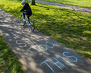 'This too shall pass', a message of hope written in chalk on the cycle path - Clapham Common is pretty quiet now Lambeth Council has taped up all the benches. The 'lockdown' continues for the Coronavirus (Covid 19) outbreak in London.