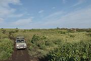 Front view of a 4x4 safari car driving along a dirt road through the Ngorongoro Highlands, Tanzania