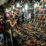 Vietnamese women look at the shoes for sale at a shoe shop in Hanoi's Old Quarter.
