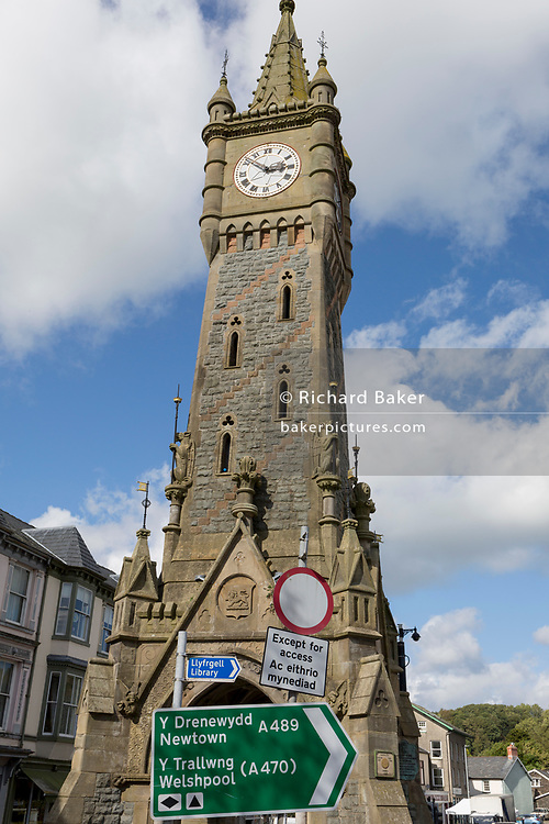 Signposts and the clocktower in Machynlleth, on 12th September 2018, in Machynlleth, Powys, Wales. To celebrate the 21st birthday of Viscount Castlereagh, the townspeople subscribed to the erection (at the town's main road intersection) of the clock tower, which has become widely known as the symbol of Machynlleth. The tower, which stands on the site of the old town hall, is the first thing many visitors will notice. The foundation stone was laid on 15 July 1874.