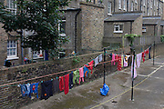 Clothing hanging on a washing line in a Pimlico housing estate in London. Reflecting a bygone era when the residents of inner-city tenements and housing estates hung out their washing on wash days (usually Mondays in the UK), relying on honesty and the community spirit to ensure their safety. Today we see this rarely apart from courtyards like this in west London. The walls are made fromclassic London stock bricks but the colours of a vibrant 21st century Britain are seen strung along the line.