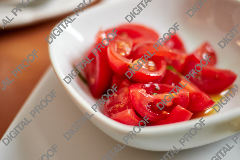 horizontal shot of fresh cherry tomatos served on a white bowl with oirl a hint of basil