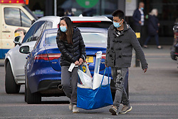 © Licensed to London News Pictures.  12/04/2021. Lonond, UK. Shoppers are seen carrying heavy bag outside IKEA at Greenwich south London as the government takes the next step on its lockdown-lifting road map and non-essential shops reopen today. Photo credit: Marcin Nowak/LNP