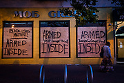 SAN FRANCISCO, CA - MAY 31: Competing words are seen spray painted on boarded up windows, following a protest over the police killing of George Floyd, outside City Hall in San Francisco, California on May 31, 2020. - The United States has erupted into days and nights of protests, violence, and looting, following the death of George Floyd after he was detained and held down by a knee to his neck, dying shortly after. (Photo by Philip Pacheco / Agence France-Presse / AFP)