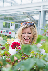 Mature woman smiling in garden centre, Augsburg, Bavaria, Germany