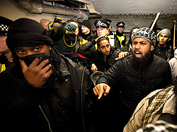 © under license to London News Pictures. 11/11/2010. Following their protest in Kensington, London, Muslims Against Crusaders were led by police along Exhibition Road and in to the Underground. They  chanted anti-democarcy slogans as they went.