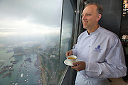 China, Hong Kong S.A.R..The Ritz-Carlton, Hong Kong. World's highest Dim Sum at Tin Lung Heen. Peter Find, Executive Chef, drinking tea and enjoying the view.