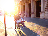 Man in suit rides bike, scooter beside him, at a stop sign in downtown Rome, Italy