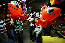 03 Feb 2006. East New Orleans, Louisiana.<br /> Tet, or Tet Nguyen Dan, Vietnamese Lunar New Year. Year of the Dog celebrations amongst the Vietnamese community of East Orleans. Stall holders peer from behind inflatable Nemos at a children's fishing game.<br /> Photo; Charlie Varley/varleypix.com