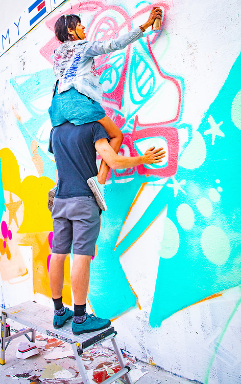 Street artist, piggybacking on her partner's shoulders, spray-paints higher sections of their mural on a shoe warehouse in Wynwood during Miami Art Week 2018.