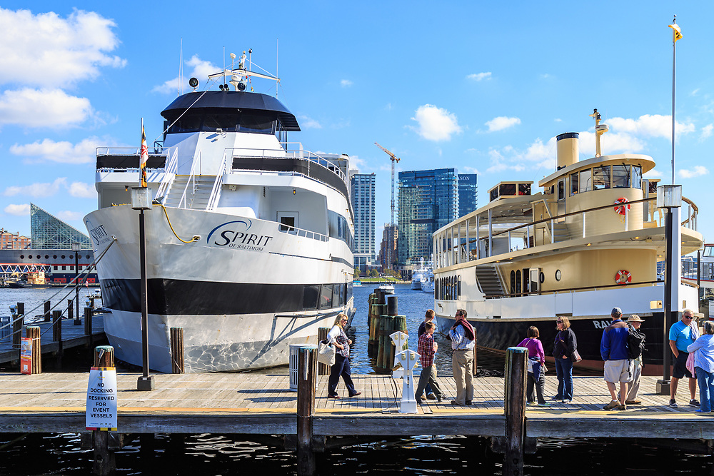 Baltimore, MD / US - October 15, 2016: Large cruise boats at dock in the city's Inner Harbor, ready to take passengers on tours of the waterway.