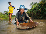 """22 APRIL 2014 - WANG NUA, LAMPANG, THAILAND: A boy watches BAENG, 60 years old, pan for gold in the Mae Wang. Villagers in the Wang Nua district of Lampang province found gold in the Mae Wang (Wang River) in 2011 after excavation crews dug out sand for a construction project. A subsequent Thai government survey of the river showed """"a fair amount of gold ore,"""" but not enough gold to justify commercial mining. Now every year when the river level drops farmers from the district come to the river to pan for gold. Some have been able to add to their family income by 2,000 to 3,000 Baht (about $65 to $100 US) every month. The gold miners work the river bed starting in mid-February and finish up  by mid-May depending on the weather. They stop panning when the river level rises from the rains. This year the Thai government is predicting a serious drought which may allow miners to work longer into the summer.    PHOTO BY JACK KURTZ"""