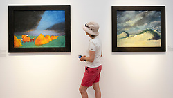 Woman looking at paintings by Emile Nolde , left, Heuernte ( Hay Making) and right Dunen ( Dunes) at Hamburger Bahnhof art museum in Berlin, Germany. .Editorial Use Only.
