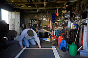 Active retired pensioner measures and cuts roofing felt in his cottage garage before winter arrives on the Isle of Skye